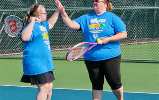 Special Olympics Minnesota tennis athletes high-fiving one another