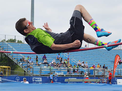 Special Olympics Minnesota high jumper jumping over bar at competition