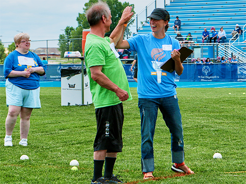 Special Olympics Minnesota volunteer and athlete high-fiving one another at athletics competition