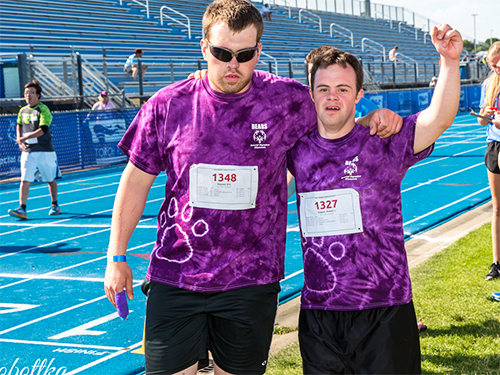 Two Special Olympics Minnesota track athletes with arms around one another at competition