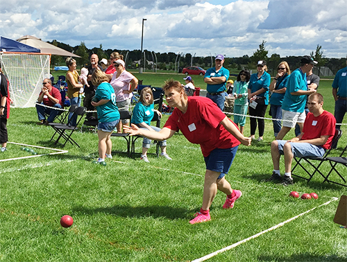 Special Olympics Minnesota bocce athlete rolling bocce ball on grass