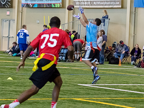 Special Olympics Minnesota flag football athlete catching football while another athlete runs in background and crowd watches from side