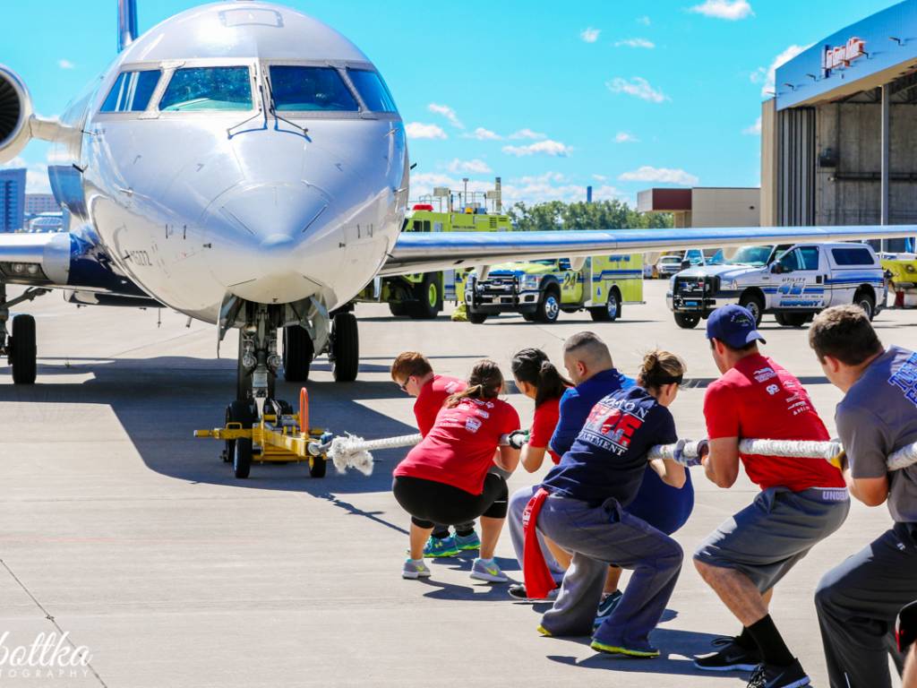 Plane Pull participants pulling rope tied to airplane