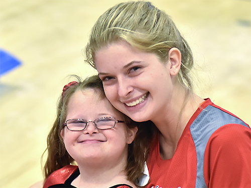 Special Olympics Minnesota athlete and volunteer smiling and embracing