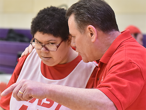 Special Olympics Minnesota coach talking to athlete at compeTition