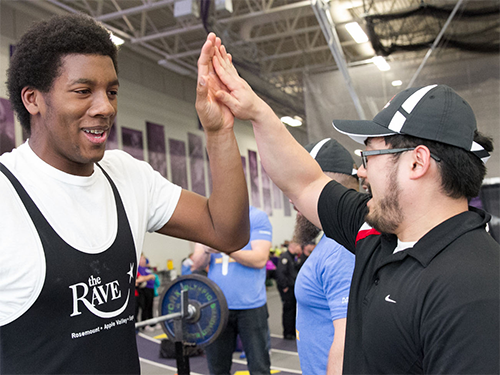 Special Olympics Minnesota coach high-fiving athlete at competition