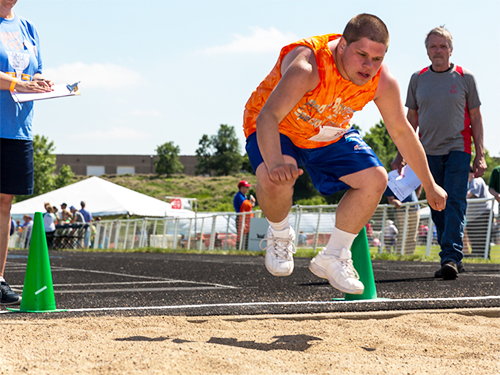 Special Olympics Minnesota long jumper jumping at competition