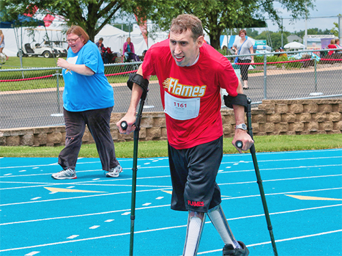 Special Olympics Minnesota track athlete using crutches while running race