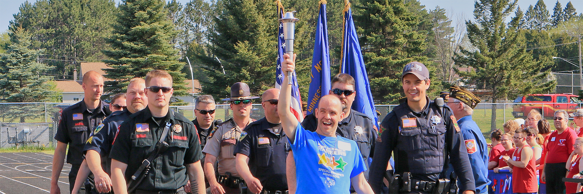 Special Olympics Minnesota athlete holding torch while marching with law enforcement officers with crowd watching from side