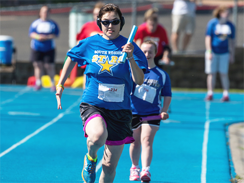 Two female Special Olympics Minnesota runners competing in a relay race