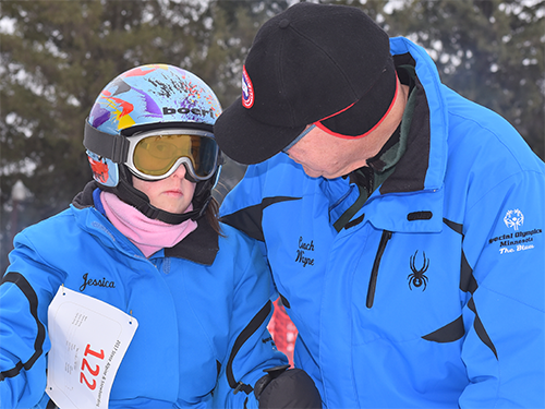 Male Special Olympics Minnesota coach talking to an alpine skiing athlete