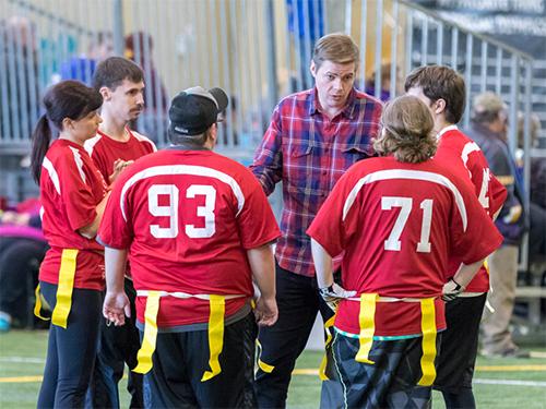 Male Special Olympics Minnesota coach talking to flag football athletes