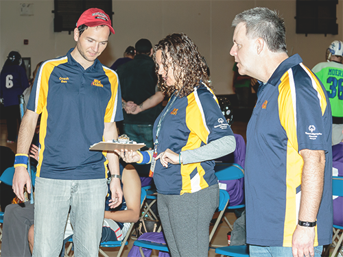 One female Special Olympics Minnesota coach and two male coaches reading a clipboard