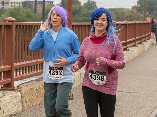 Two people running and smiling and wearing colorful wigs