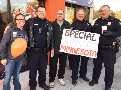 Police officers and others standing in front of Dunkin' Donuts store raising money for Special Olympics Minnesota
