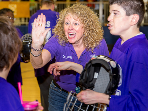 Female Special Olympics Minnesota coach giving a high five to a poly hockey athlete