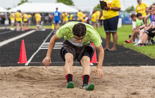 Male Special Olympics Minnesota athlete finishing a long jump