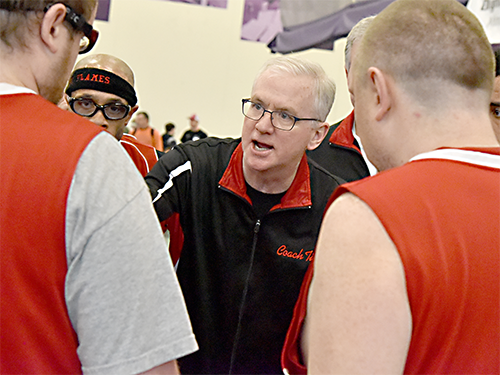 Male Special Olympics Minnesota coach talking to basketball athletes