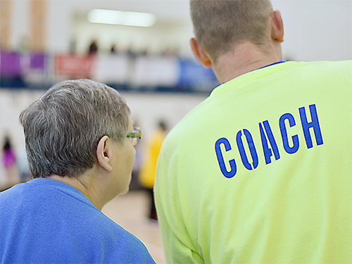 Male Special Olympics Minnesota coach wearing T-shirt that says COACH