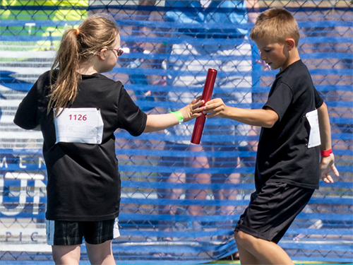 Young male Special Olympics Minnesota athlete handing off a baton to a young female athlete