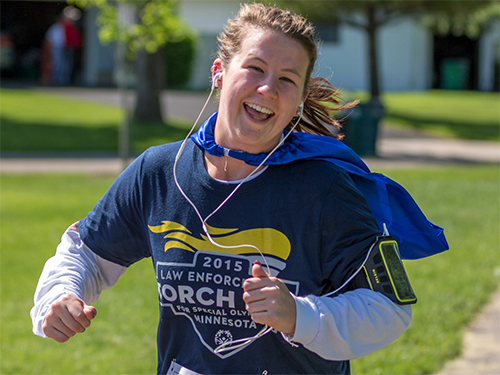 Special Olympics Minnesota runner running and smiling and wearing a cape
