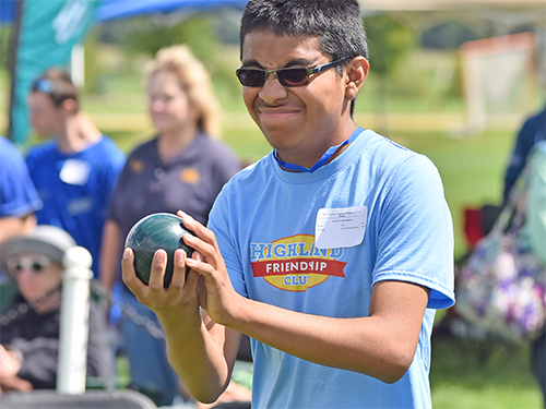 Male Special Olympics Minnesota athlete holds a bocce ball
