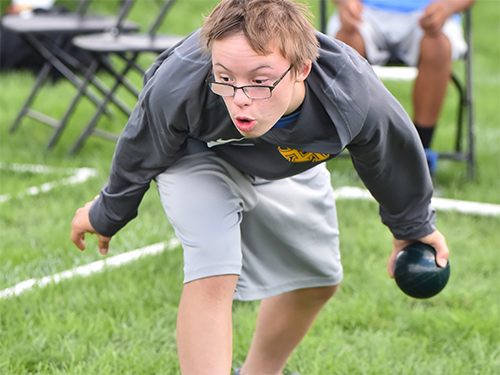 Male Special Olympics Minnesota athlete prepares to roll a bocce ball