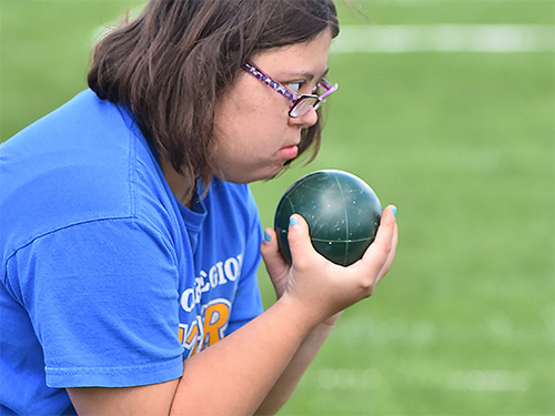 Female Special Olympics Minnesota athlete holds a bocce ball and contemplates the field