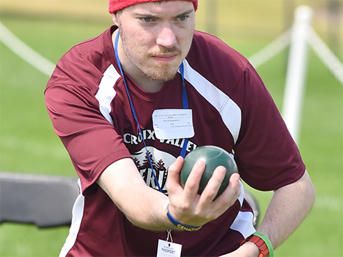 Male Special Olympics Minnesota athlete aims a bocce ball