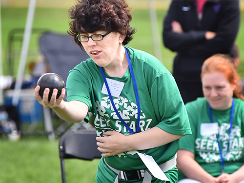 Female Special Olympics Minnesota athlete aims a bocce ball