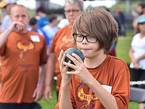 Young male Special Olympics Minnesota athlete prepares to roll a bocce ball