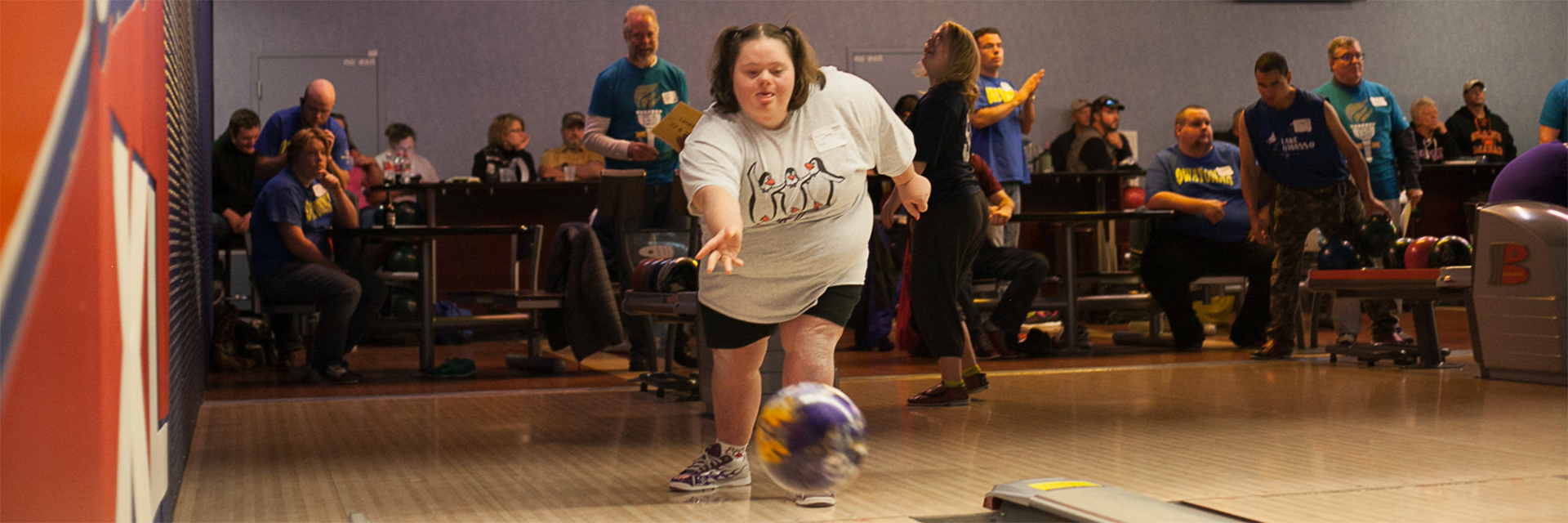 A female Special Olympics Minnesota athlete sends her purple bowling ball down the lane