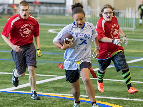 Female Special Olympics Minnesota flag football athlete runs with the ball ahead of two other athletes