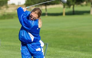 A female Special Olympics Minnesota athlete swings a golf club
