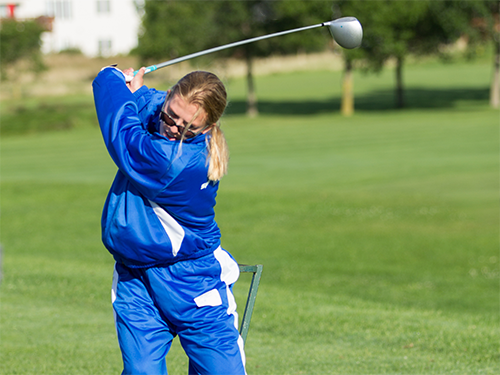A female Special Olympics Minnesota athlete swings a golf club