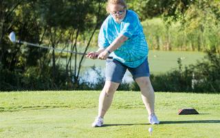 Female Special Olympics Minnesota athlete swings a golf club