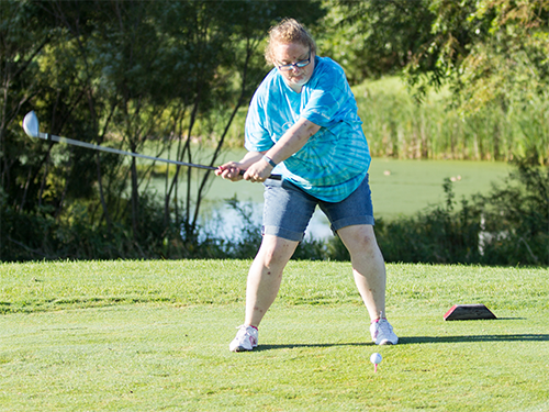 Female Special Olympics Minnesota athlete swings a golf club