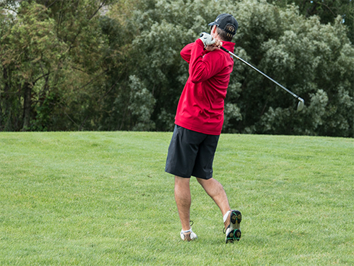 Male Special Olympics Minnesota athlete seen from behind swings a golf club