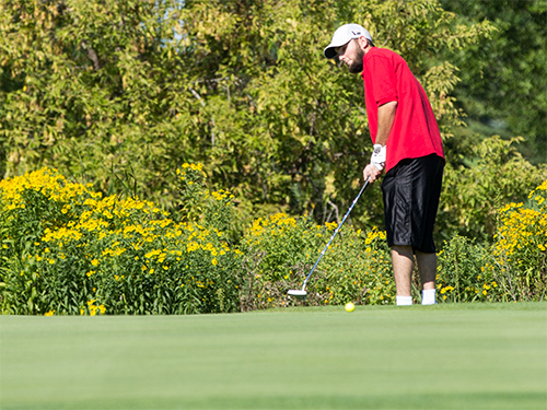Male Special Olympics Minnesota athlete holds a putter and looks at a golf green
