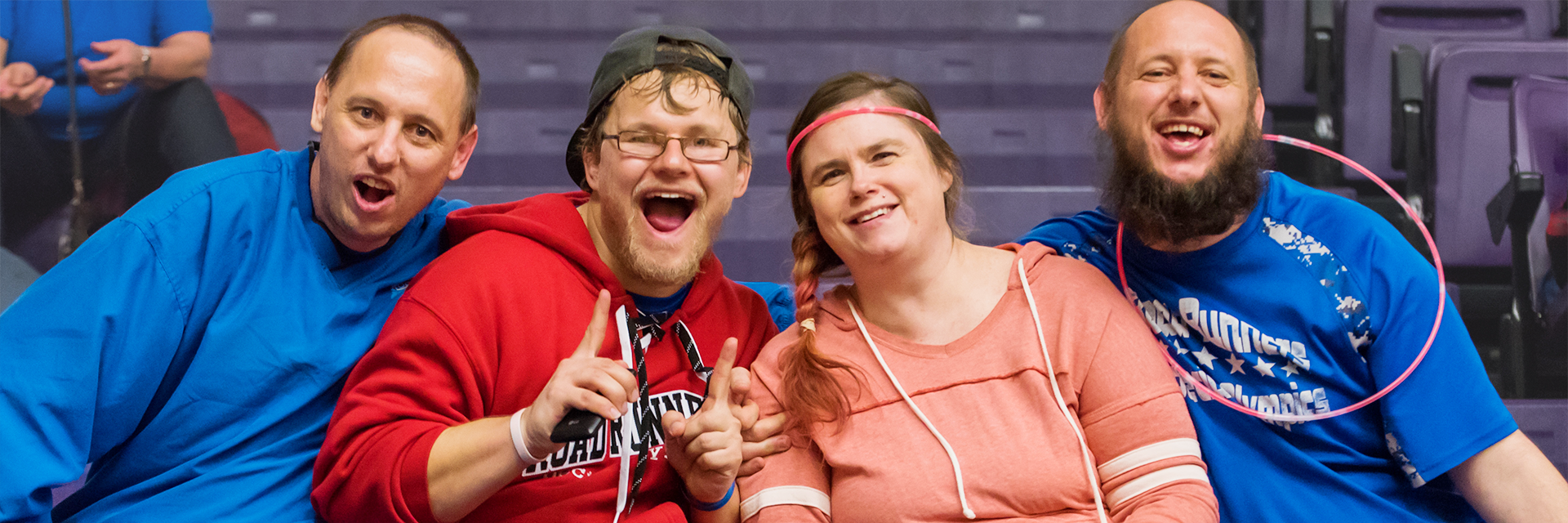 Four Special Olympics Minnesota athletes smile enthusiastically at the camera