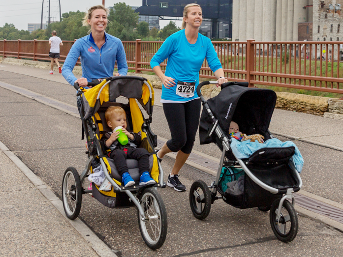 Two women pushing children in strollers while running