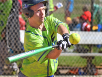 Male Special Olympics Minnesota athlete swings a bat at an approaching softball