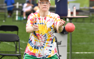 Special Olympics Minnesota athlete in a colorful tie-dyed shirt throws a bocce ball
