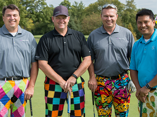 Four male golfers wearing printed pants
