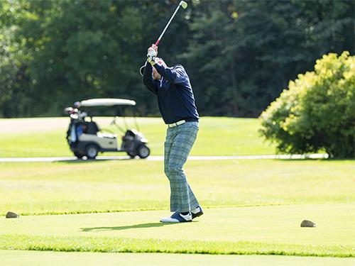 Man wearing plaid pants raises a golf club over his head
