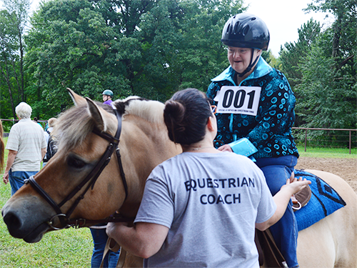 A woman wearing a shirt that says Equestrian Coach talks to a female Special Olympics Minnesota athlete riding a brown horse