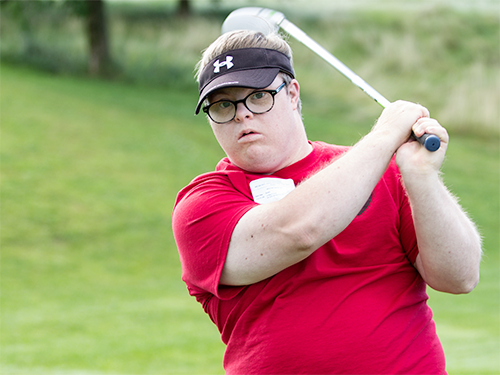 Male Special Olympics Minnesota athlete swings a golf club
