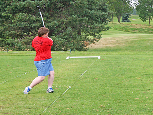 Special Olympics Minnesota golf athlete in red shirt and blue shorts swings a golf club