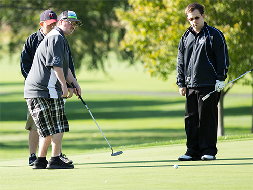 Three male Special Olympics Minnesota athletes play golf
