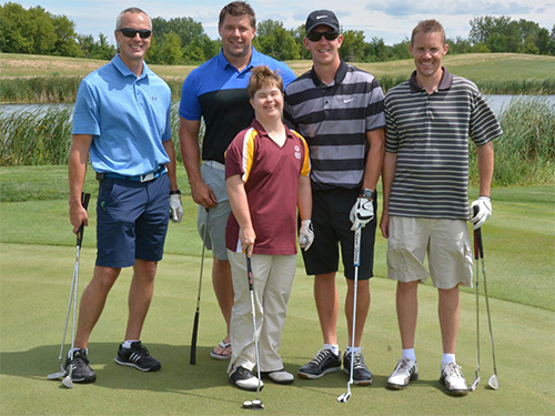 Four male golfers holding golf clubs pose with a female golfer from Special Olympics Minnesota